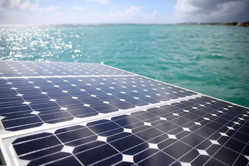 Nahaufnahme von Solar Paneelen mit Blick auf von der Sonne glitzerndes Meer symbolisiert die Nutzung von Solarenergie auf den Philippinen mit Net-Metering