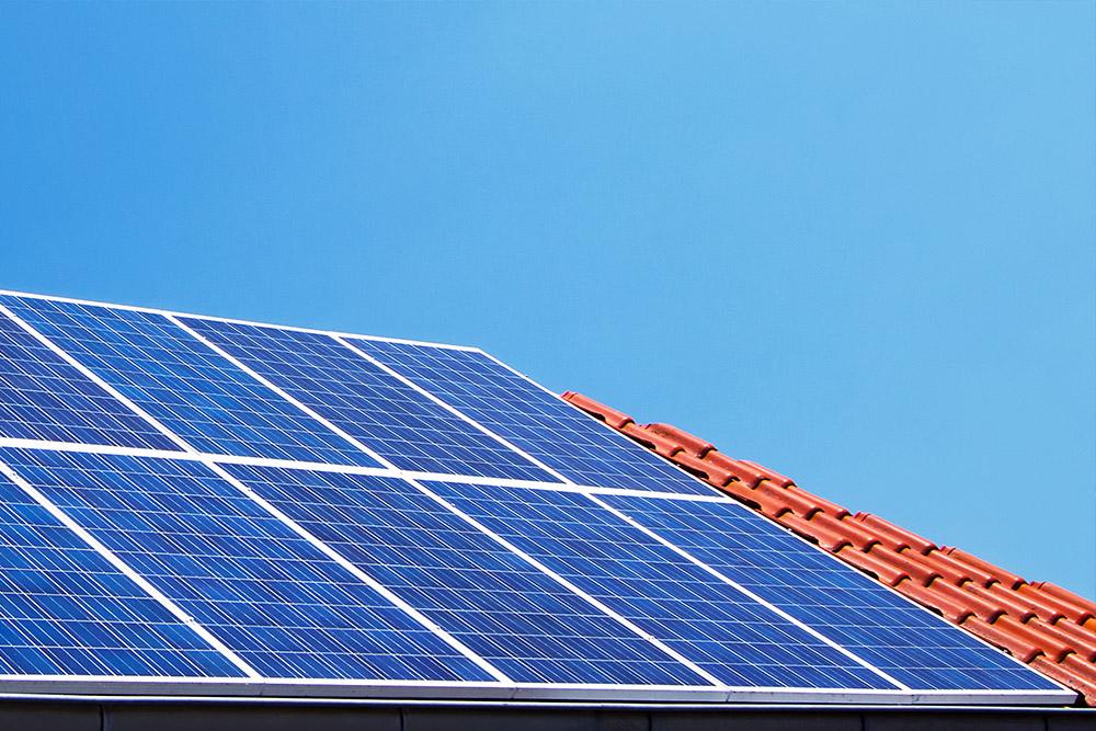 Auf einem roten, von der Sonne beschienenen Dach befinden sich mehrere Solarpaneele. Diese stehen für die Solar Dachanlagen aus Meisterhand von Meister Solar.