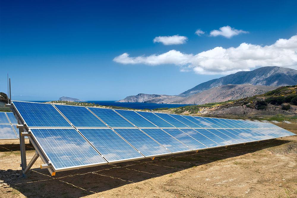 Solar Freiflächenanlage in bergiger Landschaft am Meer